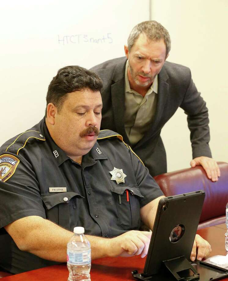 Cloud 9 CEO JC Adams aids Harris County Sheriff Deputy Fred Lerma during a training session of a telepsychiatry program Dec. 12 in Houston. Cloud 9 helped make the app a reality. Photo: Steve Gonzales, Houston Chronicle / © 2017 Houston Chronicle