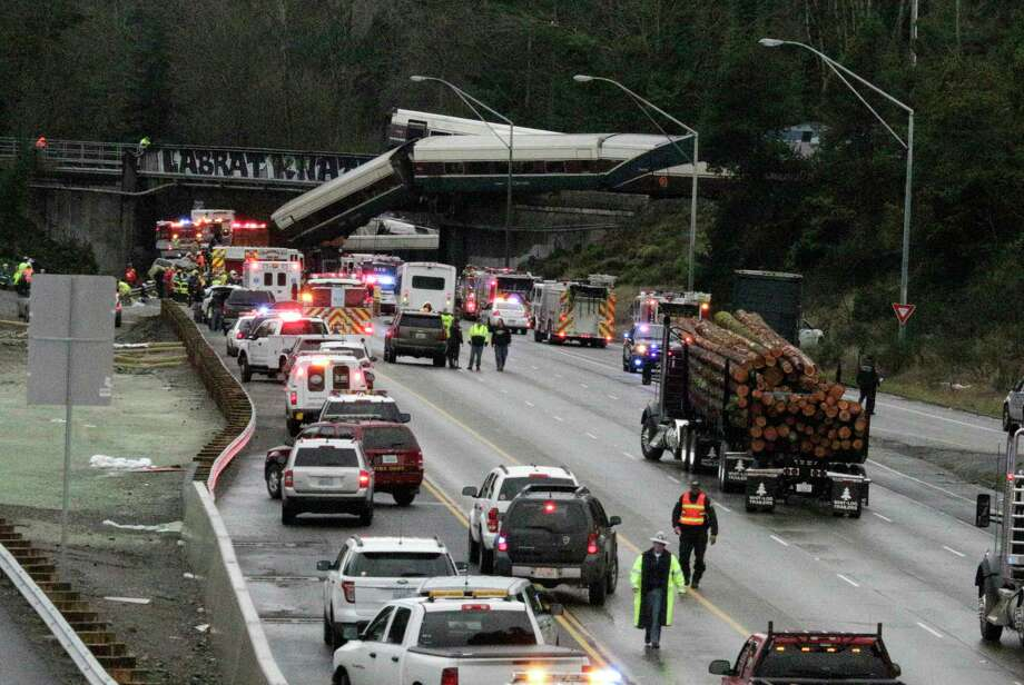 "A derailed train is seen on southbound Interstate 5 on Monday, Dec. 18, 2017, in DuPont, Wash. An Amtrak train making an inaugural run on a new route derailed south of Seattle on Monday, spilling train cars onto a busy interstate in an accident that resulted in ""multiple fatalities"" and numerous injuries, authorities said.  (AP Photo/Rachel La Corte) ORG XMIT: RPRL103 Photo: Rachel La Corte / Copyright 2017 The Associated Press. All rights reserved."