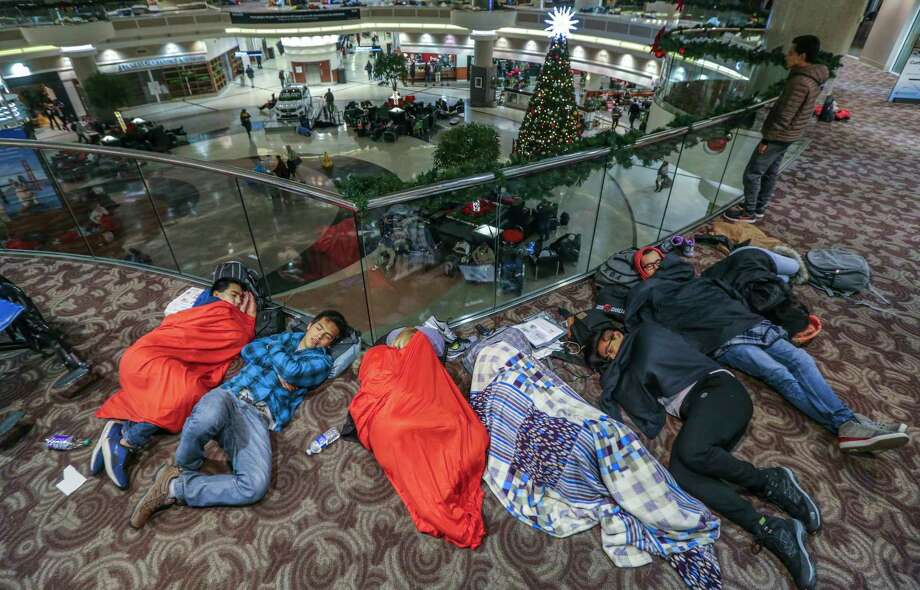 Travelers sleep in the atrium at Hartsfield-Jackson International Airport on Monday, Dec. 18, 2017, the day after a massive power outage brought operations to halt. Power was restored at the world's busiest airport after a massive outage Sunday afternoon that left planes and passengers stranded for hours, forced airlines to cancel more than 1,100 flights and created a logistical nightmare during the already-busy holiday travel season.  (John Spink/Atlanta Journal-Constitution via AP) ORG XMIT: GAATJ103 Photo: John Spink / 2017 Atlanta Journal-Constitution