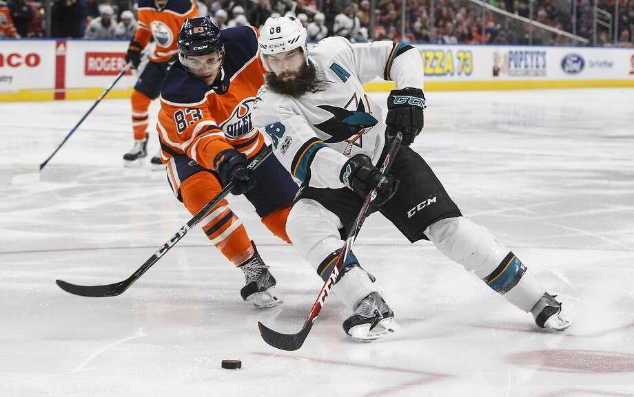 San Jose's Brent Burns is chased by Edmonton's Matthew Benning in the first period Monday night in Edmonton. Photo: Jason Franson, Associated Press
