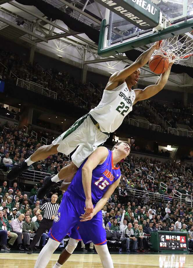 EAST LANSING, MI - DECEMBER 18: Miles Bridges #22 of the Michigan State Spartans dunks over Edward Hardt #15 of the Houston Baptist Huskies during the first half at the Jack T. Breslin Student Events Center on December 18, 2014 in East Lansing, Michigan. (Photo by Gregory Shamus/Getty Images) ORG XMIT: 775058361 Photo: Gregory Shamus / 2017 Getty Images