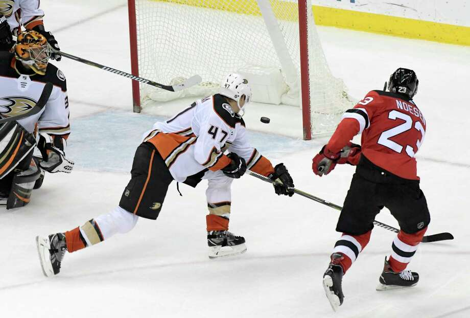 New Jersey Devils right wing Stefan Noesen (23) scores past Anaheim Ducks defenseman Hampus Lindholm (47) as Ducks goalie Ryan Miller, left, looks on during the third period of an NHL hockey game Monday, Dec.18, 2017, in Newark, N.J. (AP Photo/Bill Kostroun) ORG XMIT: NJBK109 Photo: Bill Kostroun / FR51951 AP