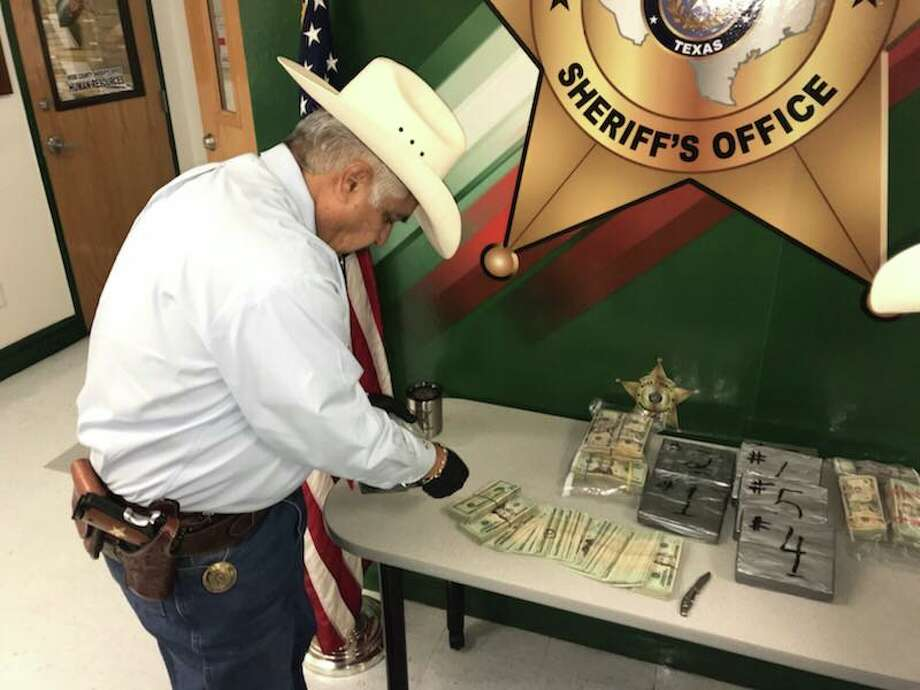 Webb County Sheriff Martin Cuellar inspects money seized recently during a traffic stop in north Laredo. Deputies allegedly confiscated about $153,000. Photo: Webb County Sheriff's Office/Courtesy