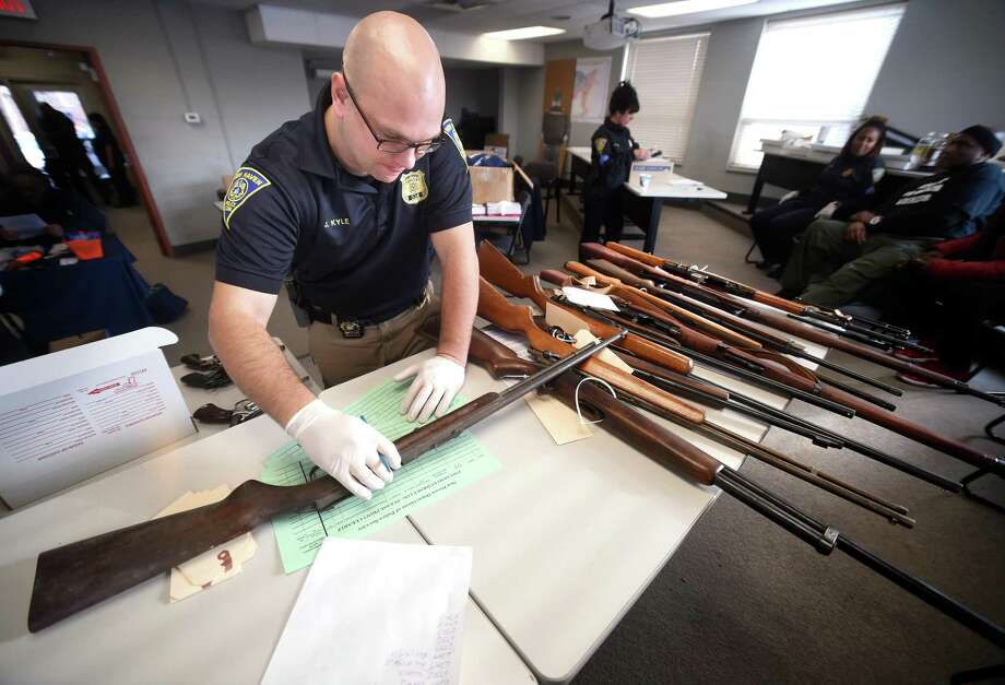 Detective Josh Kyle examines a rifle brought in during a gun buy-back  at the New Haven Police Academy in New Haven on December 16, 2017. Photo: Arnold Gold / Hearst Connecticut Media / New Haven Register