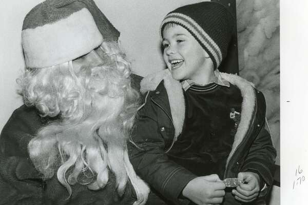 Thomas Brown, 5, shares a laugh with Santa at the courthouse. December 1984