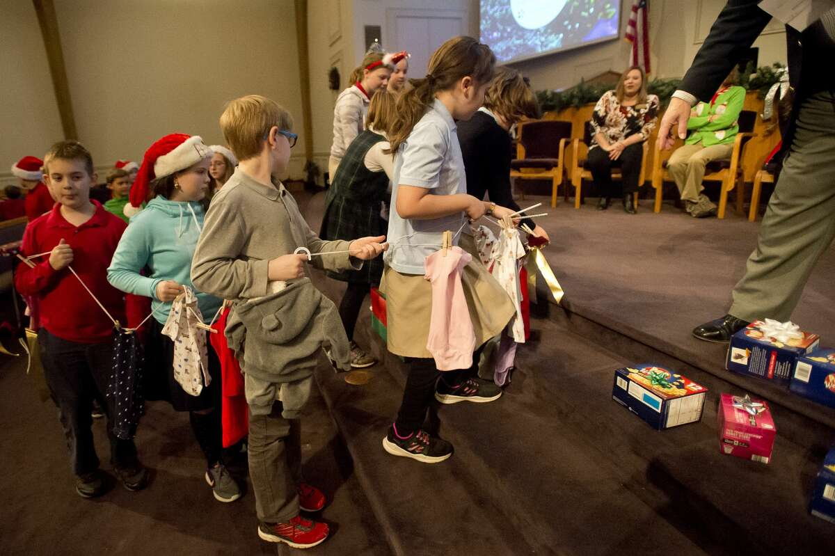 Calvary Baptist Academy students bring gifts to donate to the Pregnancy Resource Center during the school's annual Christmas Gifts for Christ Church event on Tuesday, Dec. 19, 2017. (Katy Kildee/kkildee@mdn.net)