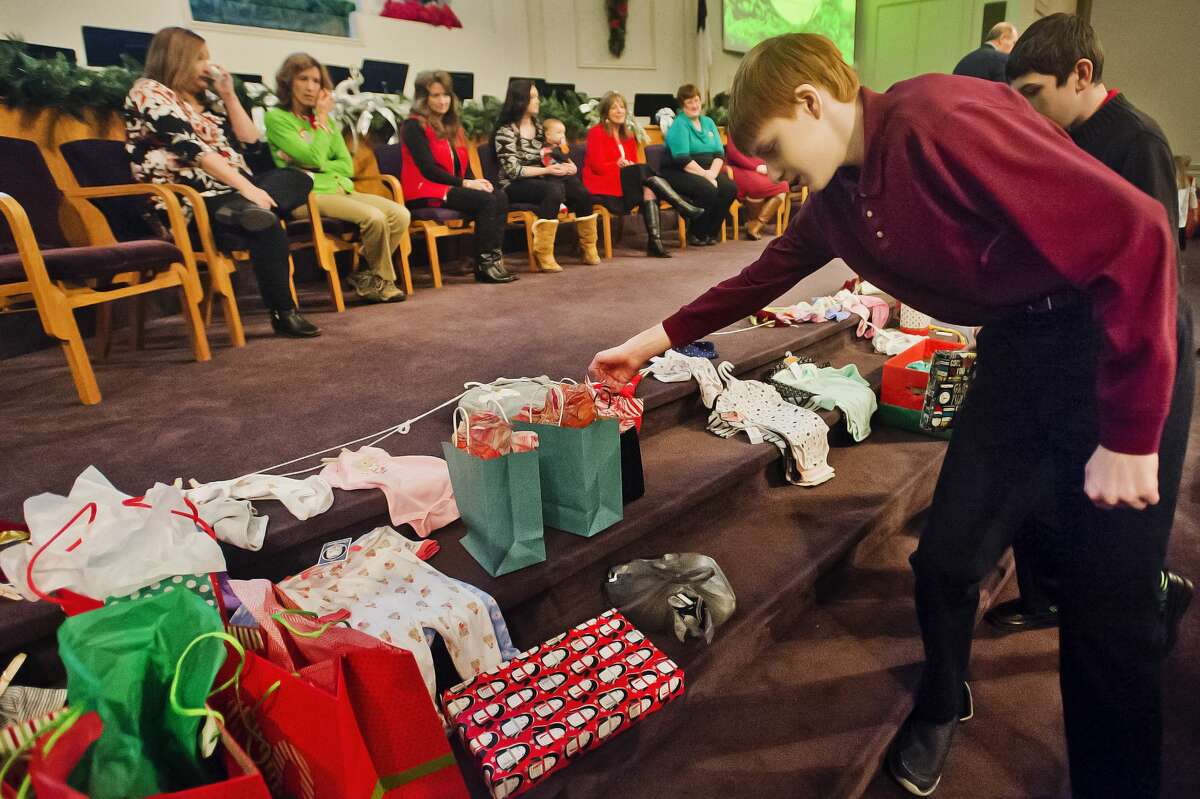 Calvary Baptist Academy student William Langer, 13, places a gift on the altar to donate to the Pregnancy Resource Center during the school's annual Christmas Gifts for Christ Church event on Tuesday, Dec. 19, 2017. (Katy Kildee/kkildee@mdn.net)