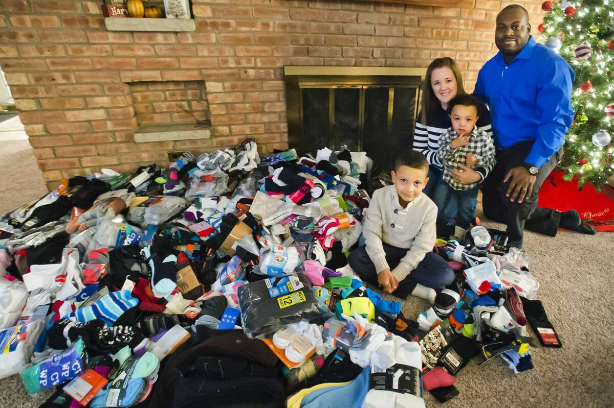 Jaxson Lewis, 6, front, poses for a photo with his parents, Katie and Brandon Lewis, and younger brother Isiah, 22 months, next to the pile of 1,428 pairs of socks Jaxson collected and donated to Midland's Open Door and the Salvation Army. (Katy Kildee/kkildee@mdn.net)