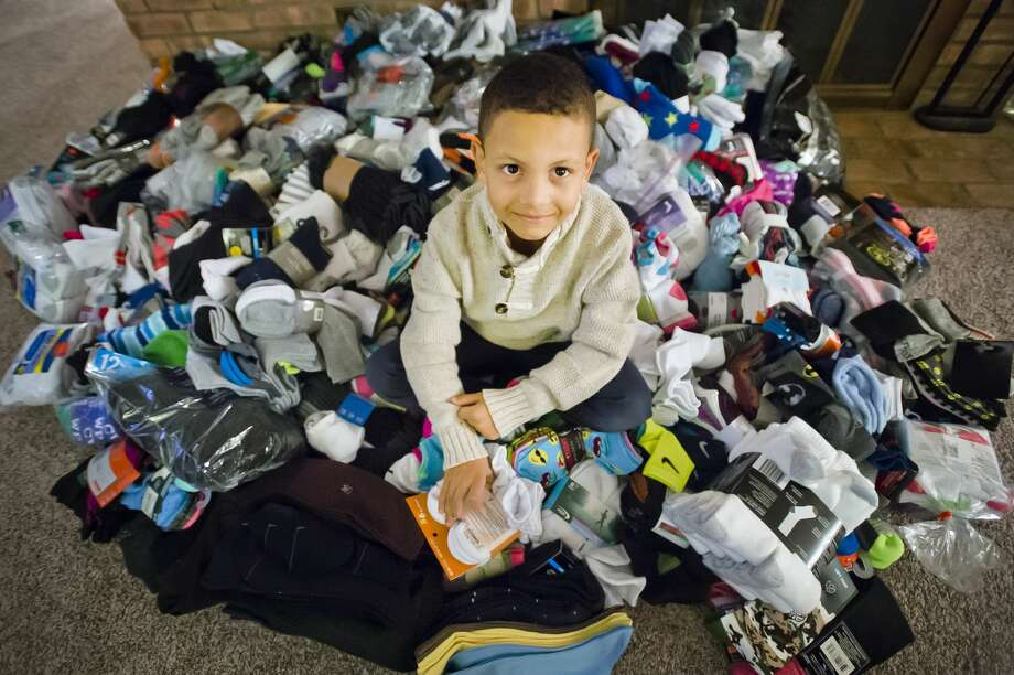 Jaxson Lewis, 6, poses for a photo next to the pile of 1,428 pairs of socks he and his family collected and donated to Midland's Open Door and the Salvation Army. (Katy Kildee/kkildee@mdn.net) Photo: (Katy Kildee/kkildee@mdn.net)