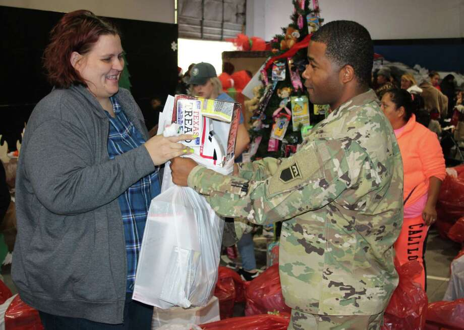 Jarrid Robertson (right) of the United States Army passes a bag of gifts to Veronica Africa (left) at the Angel Select Toy Drive. Photo: Jacob McAdams