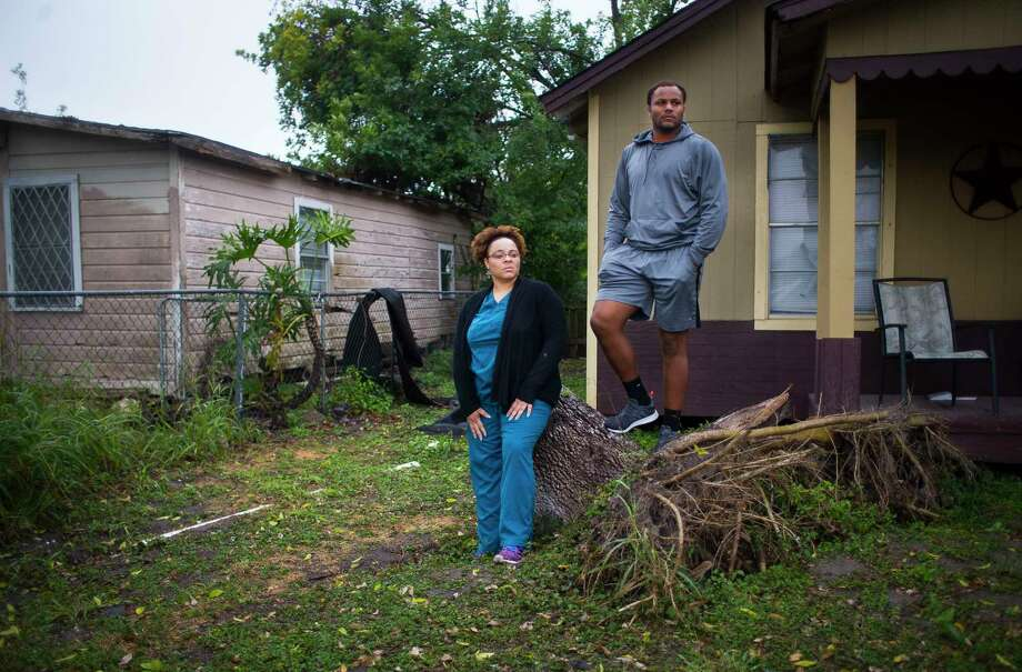 Armonie Brown, a junior lineman at Refugio High School, and his mother, LaVena Williams, stand on a tree outside their home that fell during Hurricane Harvey, Monday, Dec. 18, 2017, in Refugio. Their home needed a new roof after the storm hit the small Texas town. Photo: Mark Mulligan, Houston Chronicle / © 2017 Houston Chronicle