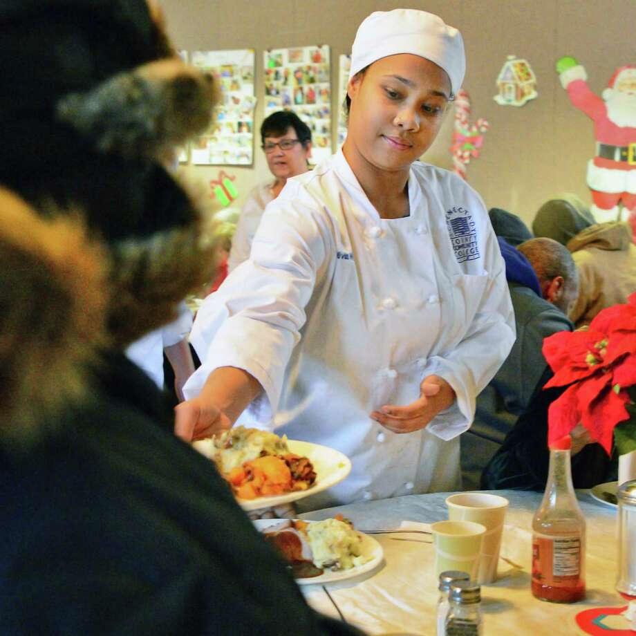 SCCC culinary student Olivia Wilborn of Albany serves holiday meals at St.John's/St. Anne's Outreach Tuesday Dec. 19, 2017 in Albany, NY.  (John Carl D'Annibale / Times Union) Photo: John Carl D'Annibale, Albany Times Union / 20042449A