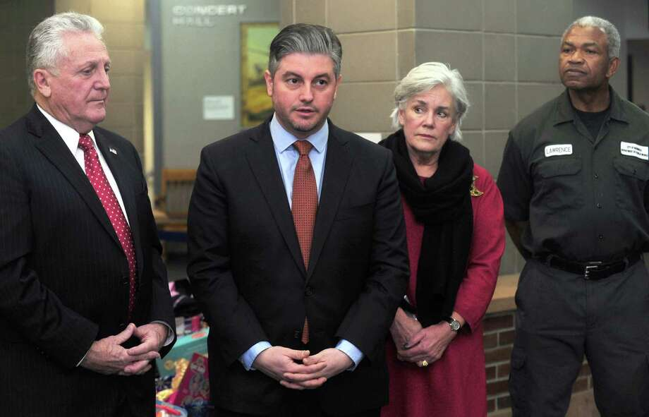 Norwalk Mayor Harry Rilling, left, and Chief of School Operations Dr. Frank Costanzo, present holiday gift baskets from City and Board of Education employees to Executive Director of Person-to-Person, Ceci Maher, second from right, as Department of Public Works employee Oliver Lawrence, looks on Tuesday, December 19, 2017, in the first-floor atrium at City Hall in Norwalk, Conn.  Photo: Erik Trautmann / Hearst Connecticut Media / Norwalk Hour