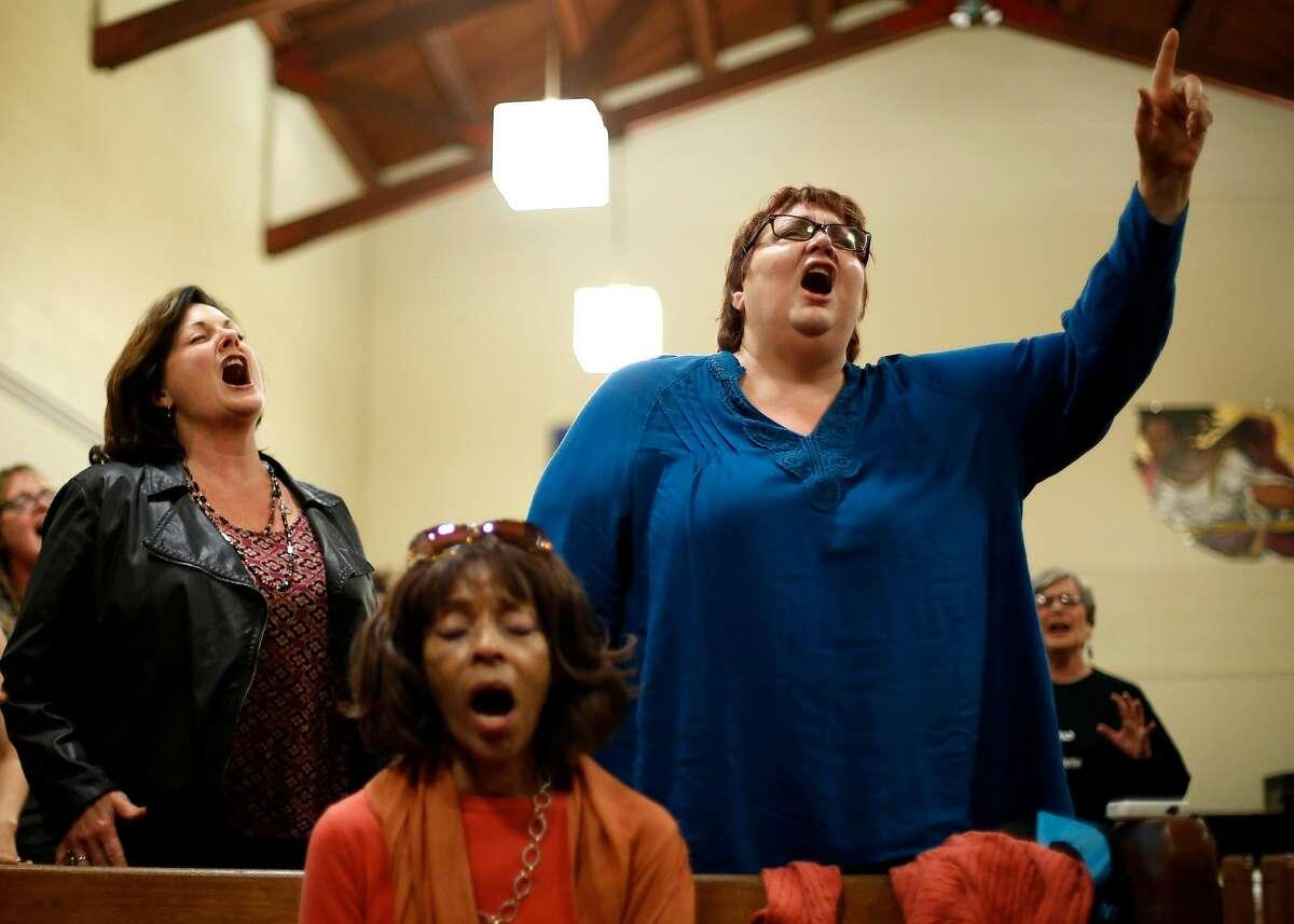 Kellie Morlock (left), Brenda Baily and Debra Sturdevant sing during an Oakland Interfaith Gospel Choir practice at the Imani Community Church in Oakland, California, on Monday, Nov. 2, 2015.