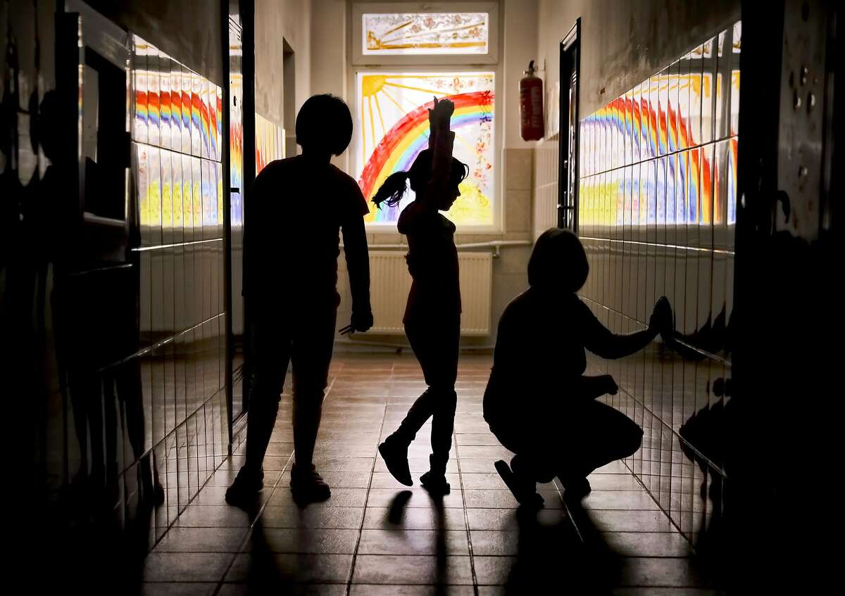 Sara, a child living at the Robin Hood orphanage, tries a ballet move while posing for a photo with other children in a corridor with painted windows, in Bucharest, Romania, on Friday, Nov. 3, 2017. One of the old-style orphanages still operating in Bucharest, it is due to close in 2018. Children who can't be reunited with their families or placed in foster care will move into state-supervised family-style homes. (AP Photo/Vadim Ghirda)