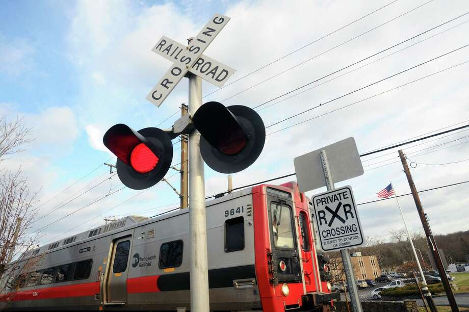 A Grand Central Terminal-bound MetroNorth train crosses an intersection on Largo Drive in the Springdale neighborhood of Stamford, Conn. on Tuesday, Dec. 19, 2017. Gov. Dannel P. Malloy on Wednesday announced that all Connecticut rail lines have been equipped with a safety system called Positive Train Control. Photo: Michael Cummo, Hearst Connecticut Media / Stamford Advocate