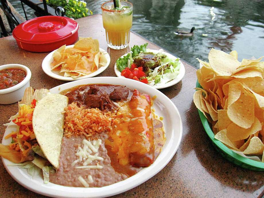 The Deluxe Dinner at Casa Rio includes a cheese enchilada, a tamal, a crispy taco, chile con carne, rice, beans, queso and a guacamole salad. Jalapeño margarita and duck not included. Photo: Mike Sutter /San Antonio Express-News