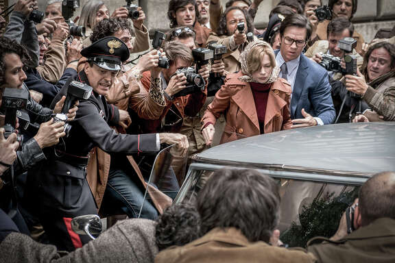 "Gail Harris (Michelle Williams, in scarf) and Fletcher Chace (Mark Wahlberg, in glasses) are mobbed by paparazzi in ""All the Money in the World."""