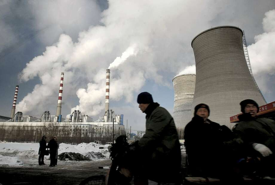 "In this file photo, workers cycle past a coal-fired power plant on a tricycle cart in Changchun, in northeast China's Jilin province. Carbon dioxide concentrations - whose ""greenhouse gas effect"" traps heat  and drives climate change - were around 280 parts per million circa  1880, at the dawn of the industrial revolution. They're now 46 percent  higher. Photo: ASSOCIATED PRESS"