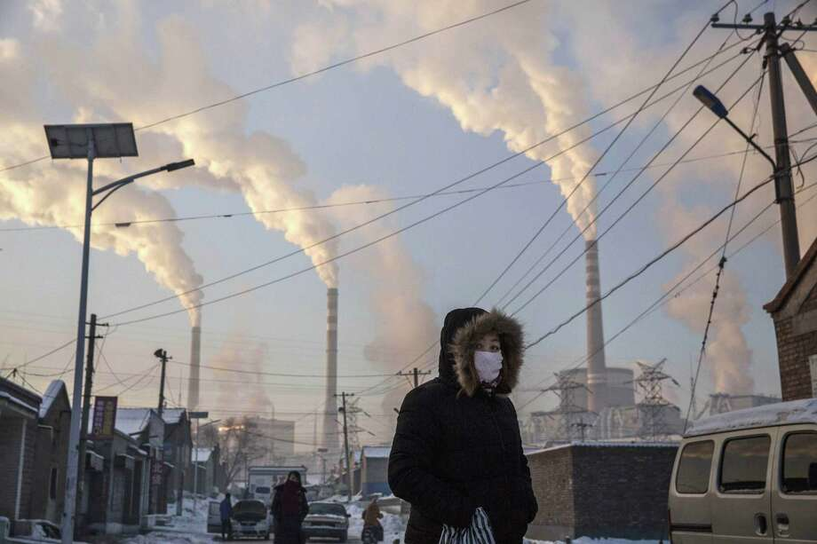 Smoke billows from stacks as a Chinese woman wears as mask while walking in a neighborhood next to a coal fired power plant on November 26, 2015 in Shanxi, China. A history of heavy dependence on burning coal for energy has made China the source of nearly a third of the world's total carbon dioxide (CO2) emissions, the toxic pollutants widely cited by scientists and environmentalists as the primary cause of global warming. China's government has publicly set 2030 as a deadline to reach the country's emissions peak, and data suggest the country's coal consumption is already in decline. The governments of more than 190 countries are expected to sign an agreement in Paris to set targets on reducing carbon emissions in an attempt to forge a new global agreement on climate change.  (Photo by Kevin Frayer/Getty Images) *** BESTPIX *** Photo: Kevin Frayer, Stringer / Getty Images / 2015 Getty Images