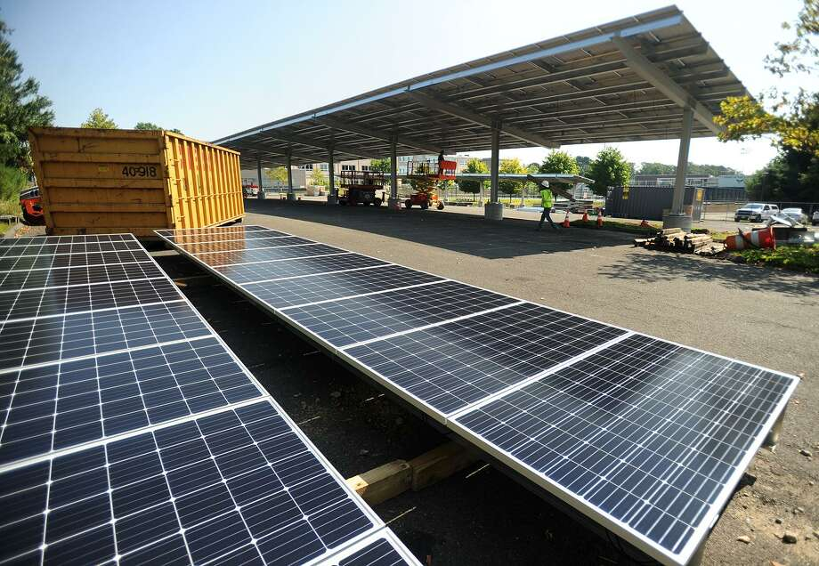 Workers install massive solar power arrays above the student parking lot at Fairfield Ludlowe High School & Bethel hopes to install solar canopies at town hall - NewsTimes