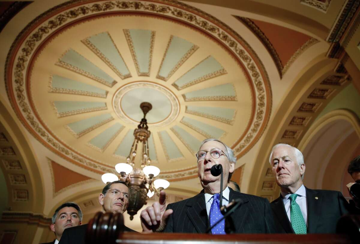 Senate Majority Leader Mitch McConnell of Ky., second from right, speaks after their caucus luncheon, with Sen. Cory Gardner, R-Colo., left, Sen. John Barrasso, R-Wyo., and Sen. John Cornyn, R-Texas, right, on Capitol Hill, Tuesday, Dec. 19, 2017 in Washington.
