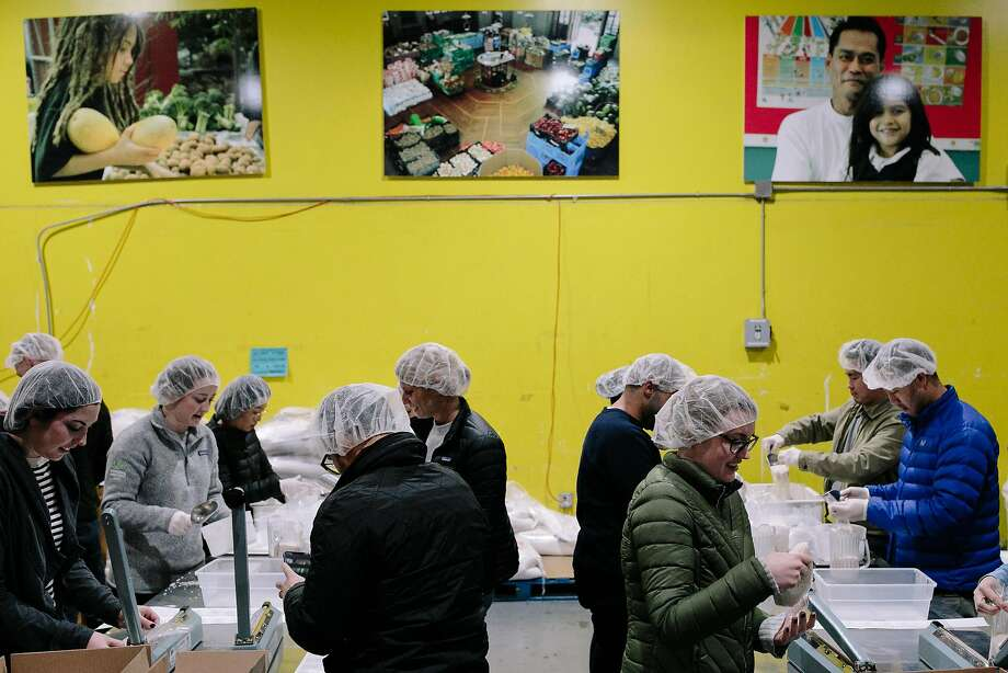 Volunteers package rice at the S.F.-Marin Food Bank in San Francisco Monday. The bank was one of several that stepped up distribution efforts to aid those displaced by October's Wine Country wildfires. Photo: Mason Trinca, Special To The Chronicle