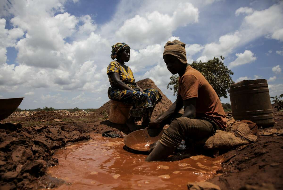 Under the watchful eye of his boss, an underage youth from Burundi works with mercury in an artisanal gold mine in North West Tanzania on Thursday, February 23, 2017. Large mines have to follow regulations, such as age of workers. But the smaller mines can circumvent such regulations.