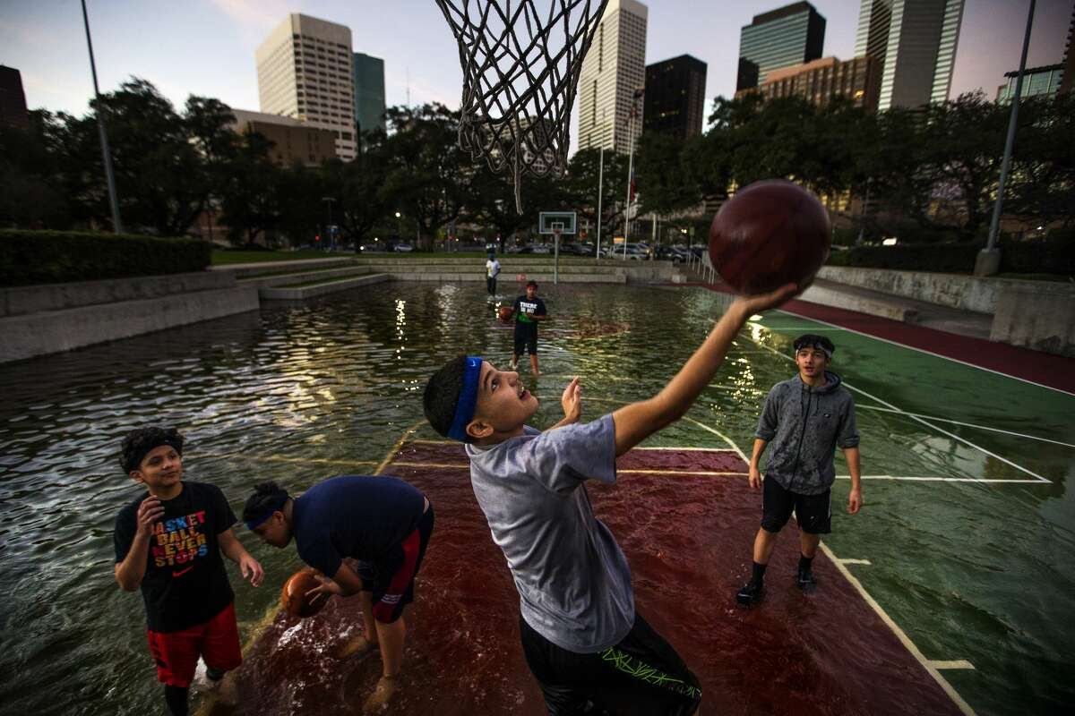Angel Charles, 13, drives to the hoop as he and his friends play basketball in a court filled with rain water from the morning's storms outside the Toyota Center where the Houston Rockets are set to take on the Washington Wizards Monday, Jan. 2, 2017 in Houston.