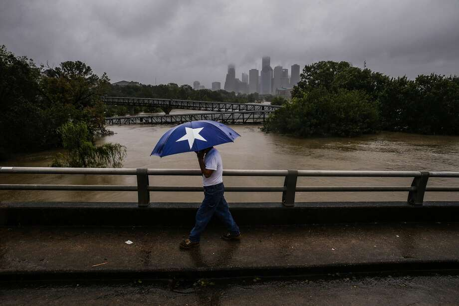 Armando Bustamante walks along Studemont Street over Buffalo Bayou as flood waters from Tropical Storm Harvey flow toward downtown Houston Tuesday, Aug. 29, 2017. Photo: Michael Ciaglo/Houston Chronicle