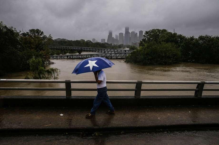 Armando Bustamante walks along Studemont Street over Buffalo Bayou as flood waters from Tropical Storm Harvey flow toward downtown Houston Tuesday, Aug. 29, 2017. Photo: Michael Ciaglo/Houston Chronicle