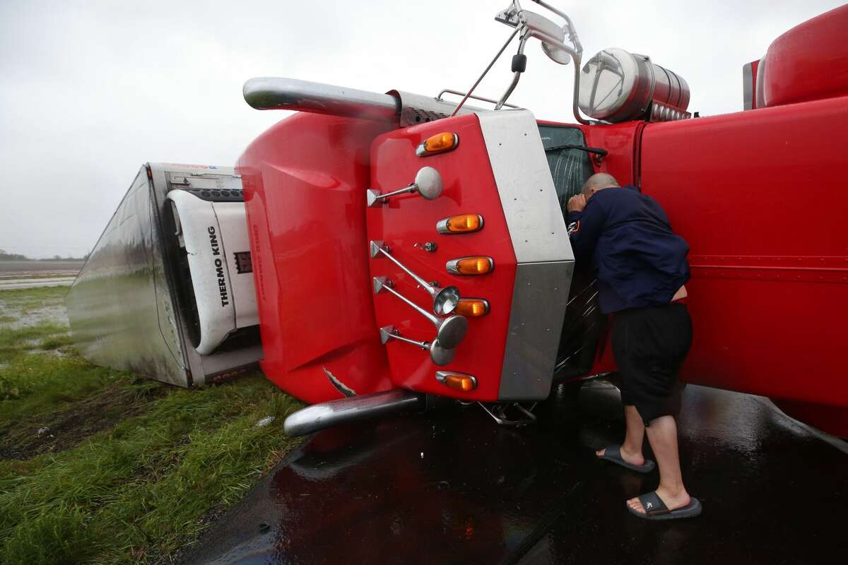 Dave McGrew looks into the cabin of an 18-wheeler that was flipped on its side on Highway 59 West as Hurricane Harvey hit the Central Gulf Coast Saturday, Aug. 26, 2017, in Texas. McGrew stopped while on his way to check on his family in Victoria, Texas.