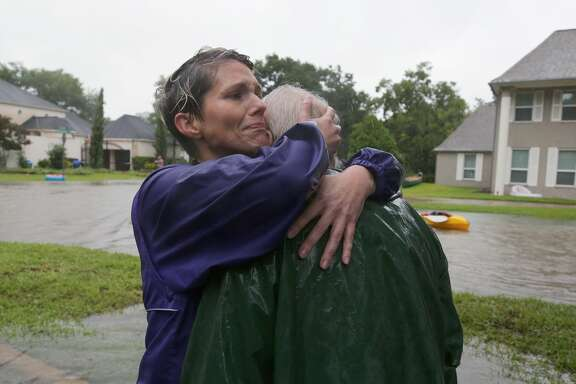 Amanda Ankney hugs her father Byron Gilleon after he was rescued from his homes near Crossroads and Walkwood drives during Tropical Storm Harvey Monday, Aug. 28, 2017, in Houston.