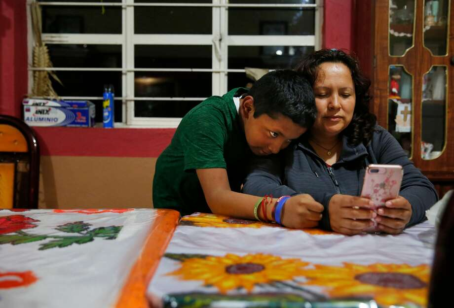 Jesus Sanchez, 12, and his mother, Maria Mendoza-Sanchez, video-chat with his sisters back in Oakland. Photo: Leah Millis, The Chronicle