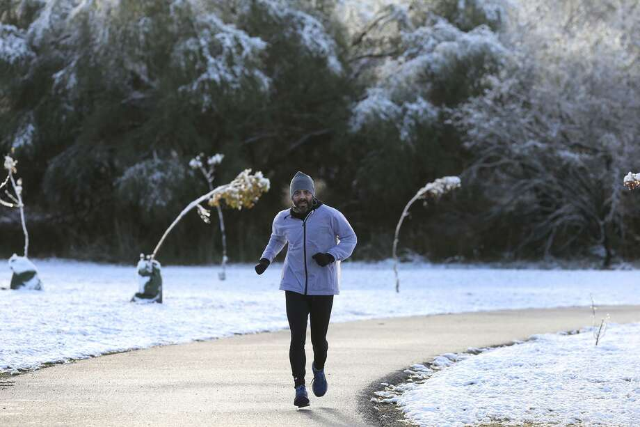 A jogger runs along a path at McAllister Park the morning after the recent snowfall. A reader theorizes — sarcastically — that climate change contributed to the snow. Photo: John Davenport /San Antonio Express-News / ©John Davenport/San Antonio Express-News