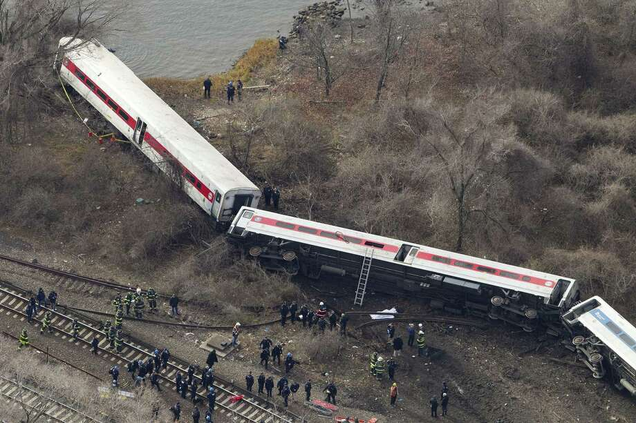 Emergency rescue personnel work the scene of a Metro-North passenger train derailment in the Bronx borough of New York, Sunday, Dec. 1, 2013. The train derailed on a curved section of track on Sunday morning, coming to rest just inches from the water and causing multiple fatalities and dozens of injuries, authorities said. Metropolitan Transportation Authority police say the train derailed near the Spuyten Duyvil station. Photo: Mark Lennihan / Associated Press / AP