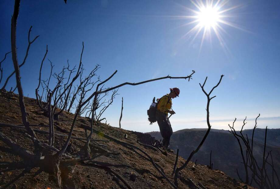 In the Thomas Fire zone, Santa Barbara County Fire Capt. Ryan Thomas hikes down steep terrain to meet with his crew and root out and extinguish smoldering hot spots in Santa Barbara. Photo: Mike Eliason / Mike Eliason / Santa Barbara County Fire Department / Santa Barbara County Fire Department