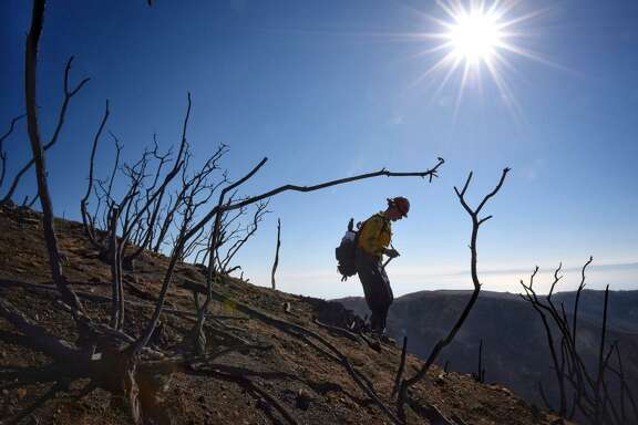 In the Thomas Fire zone, Santa Barbara County Fire Capt. Ryan Thomas hikes down steep terrain to meet with his crew and root out and extinguish smoldering hot spots in Santa Barbara.