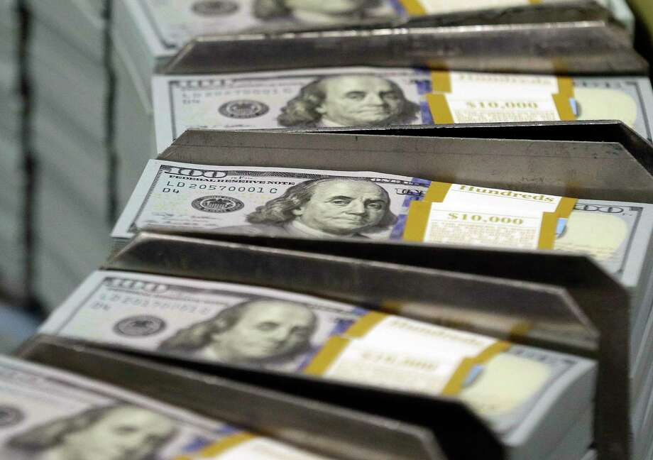 FILE - In this Sept. 24, 2013, file photo, just cut stacks of $100 bills make their way down the line at the Bureau of Engraving and Printing Western Currency Facility in Fort Worth, Texas. Big U.S. companies have been piling up cash for years, but have spent little of it on buying equipment and raising wages and other things to grow the economy. Republicans say they know how to fix this: Give companies even more money by cutting their taxes. (AP Photo/LM Otero, File) Photo: LM Otero, STF / AP2013