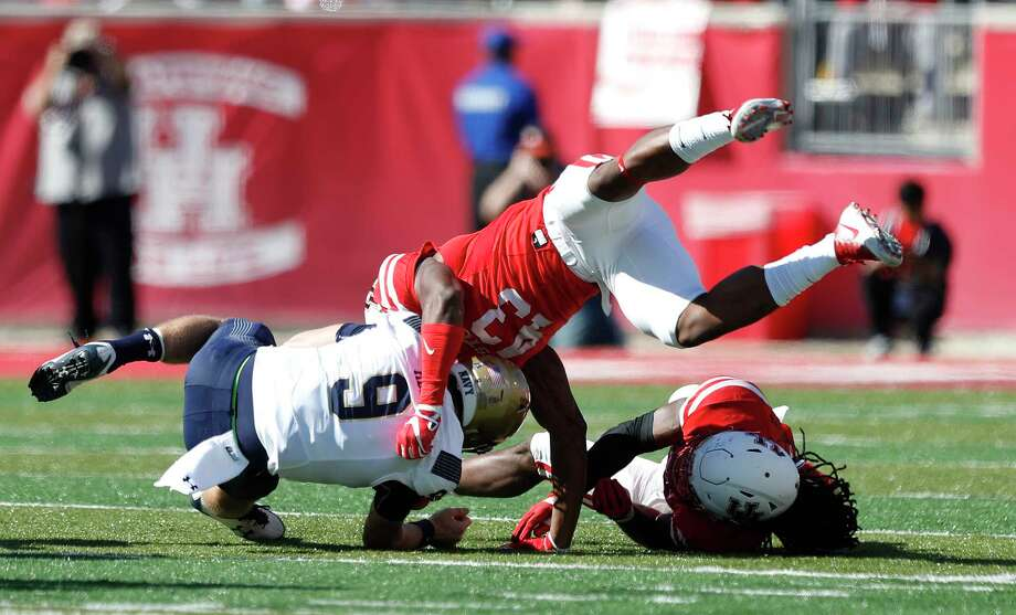 UH sophomore Leroy Godfrey, who had 81/2 sacks in his first season as a starter, gets to Navy quarterback Zach Abey in acrobatic style. Photo: Karen Warren, Staff / © 2017 Houston Chronicle