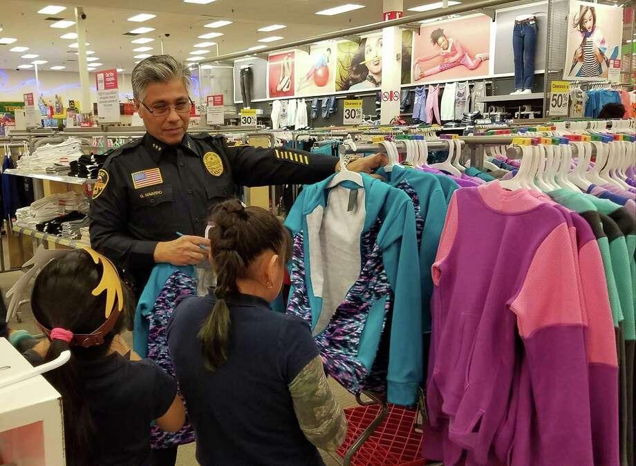 Un oficial de policía ayuda a dos estudiantes de Cuellar Elementary mientras buscan en que gastar su tarjeta de regalo de Target del program Heroes and Helpers. Photo: Foto De Cortesía