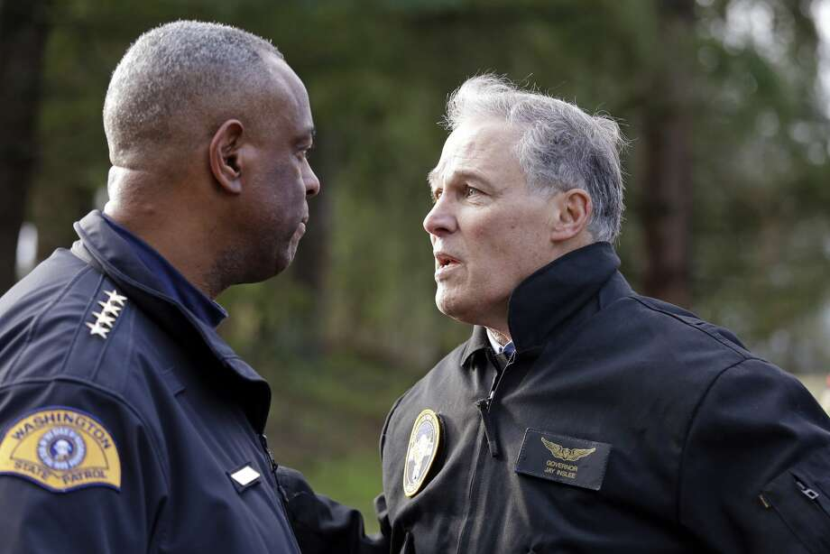 """Washington Gov. Jay Inslee, right, talks with Washington State Patrol Chief John Batiste. Inslee enacted a moratorium on the death penalty in Washington in 2014. He praised the State Senate for Friday's vote to abolish capital punishment, saying: """"One step closer to justice for all."""" Photo: Elaine Thompson/AP"""