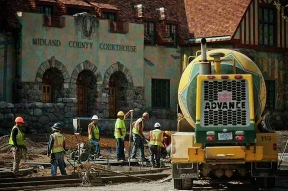 Construction workers make progress on the downtown streetscape project last week in front of the Midland County Courthouse. (Katy Kildee/kkildee@mdn.net)