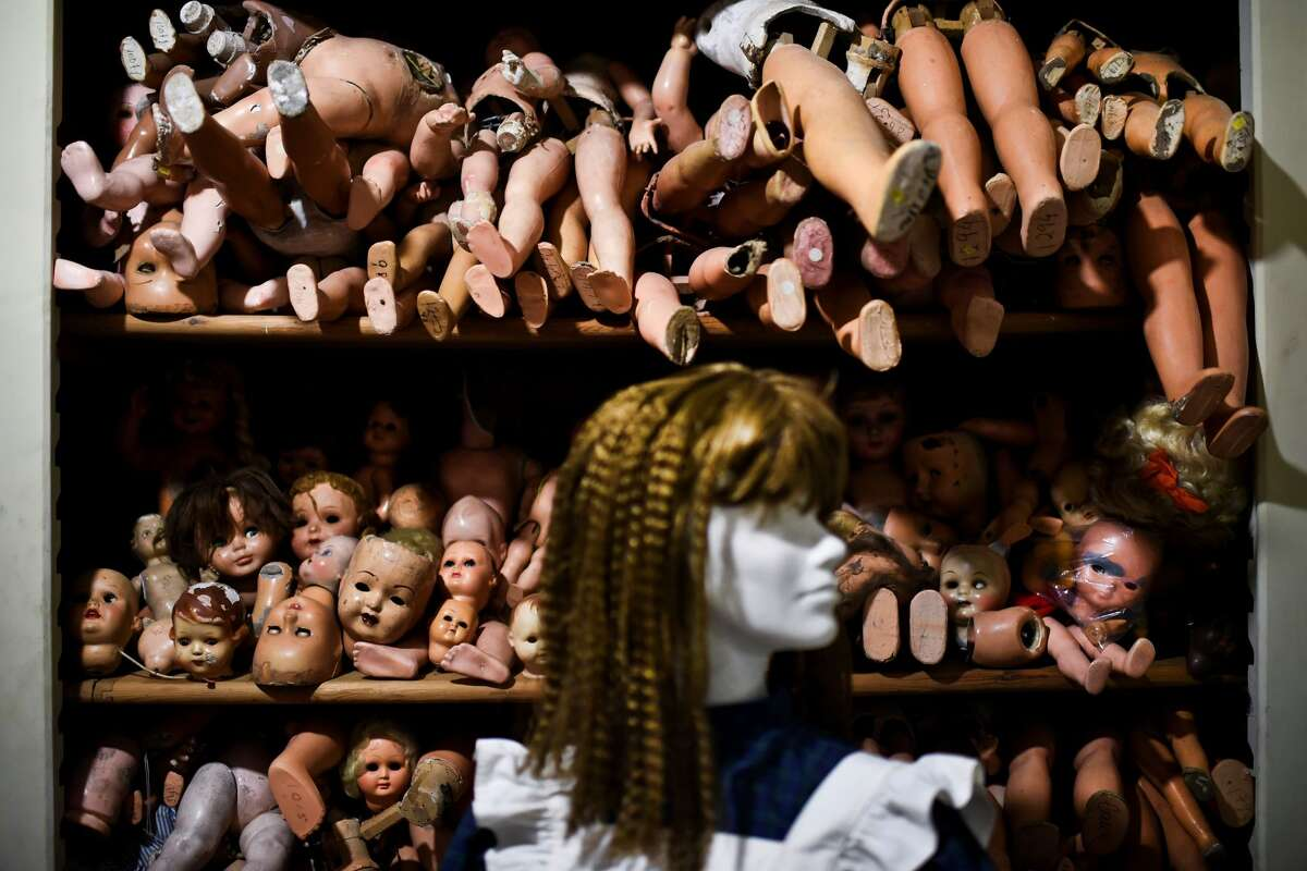 A mannequin is displayed in front of shelves of doll parts at the Doll Hospital in Lisbon on December 12, 2017. These delicate toys have been restored or collected with care and affection for five generations, at the