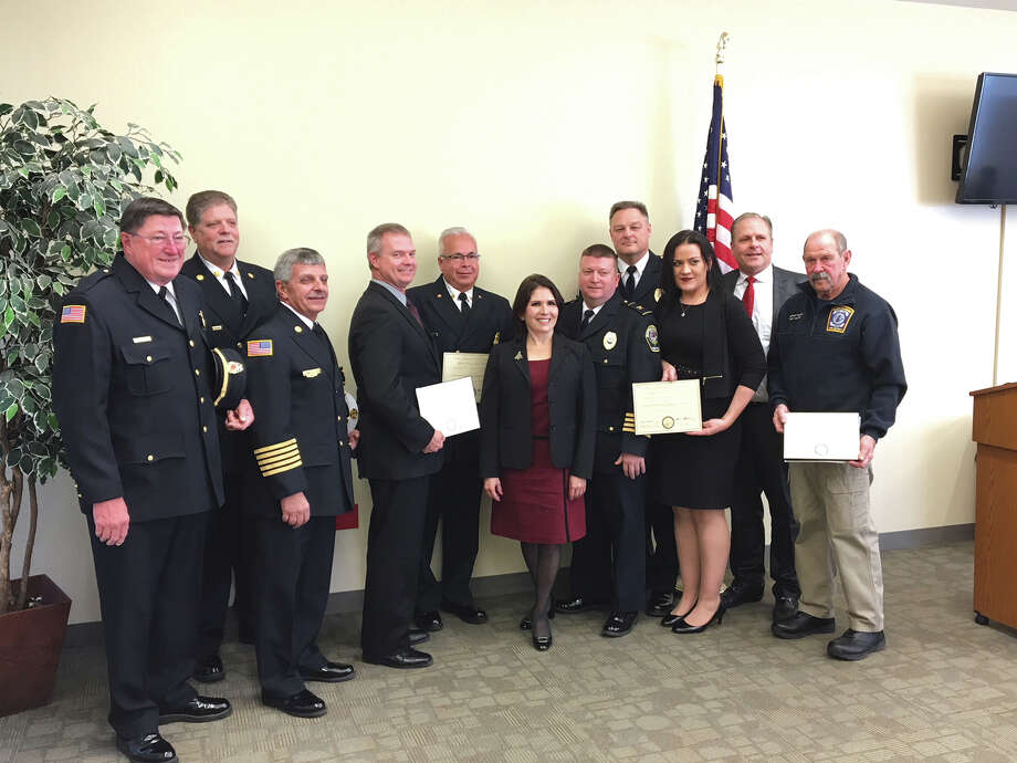 "Illinois Lt. Gov. Evelyn Sanguinetti, center, is pictured with officials from Glen Carbon, Maryville, the Glen Carbon Fire Protection District and Troy Fire Protection District. Sanguinetti was at the Glen Carbon Police Department to honor the departments as one of the best examples of ""Shared Service Best Practices"" in the state. The emergency services in the municipalities of Glen Carbon, Maryville and Troy recently entered into an intergovernmental agreement for a consolidated emergency dispatch service. Each unit of government shares in the services and costs for one emergency dispatch center and public safety answering point. The consolidated system saves taxpayer money and allows the first responders to provide better service to residents. Photo: John Sommerhof • Jsommerhof@edwpub.net"