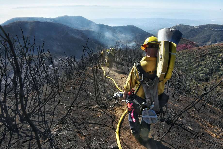 Santa Barbara County Firefighters haul dozens of pounds of hose and equipment down steep terrain to root out and extinguish smoldering hot spots in Santa Barbara on Tuesday, Dec. 19, 2017. Officials estimate that the Thomas Fire will grow to become the biggest in California history before full containment. Photo: Mike Eliason, Associated Press