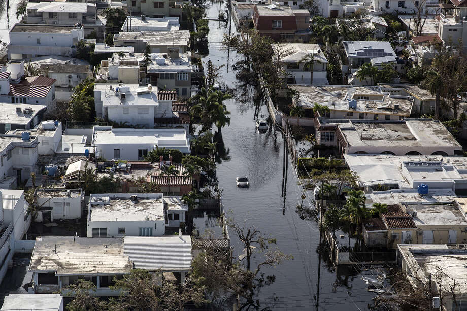 A vehicle drives through flooded streets past destroyed homes caused by Hurricane Maria in this aerial photograph taken above Barrio Obrero in San Juan, Puerto Rico, on Sept. 25, 2017. ( Photo: Alex Wroblewski/Bloomberg) / Bloomberg