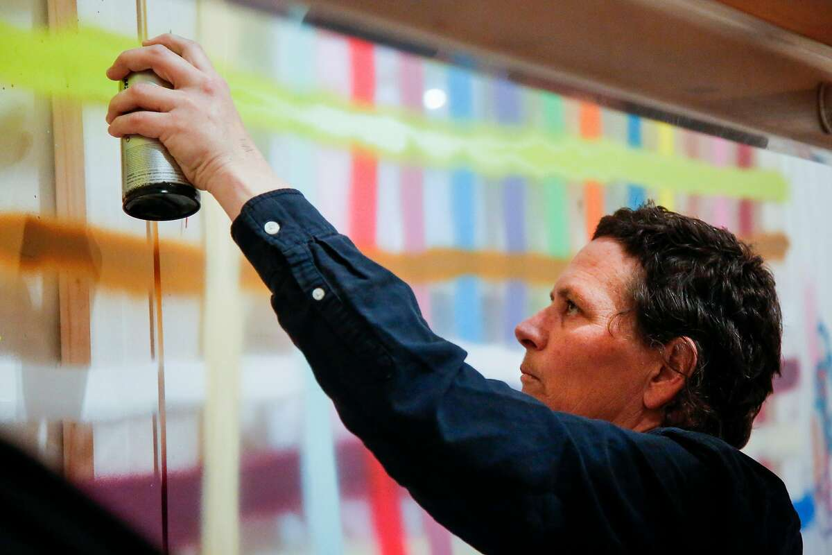 Alicia McCarthy works on her exhibit, a large piece on plexiglas, in the San Francisco Museum of Modern Art in San Francisco on Friday, June 23, 2017.