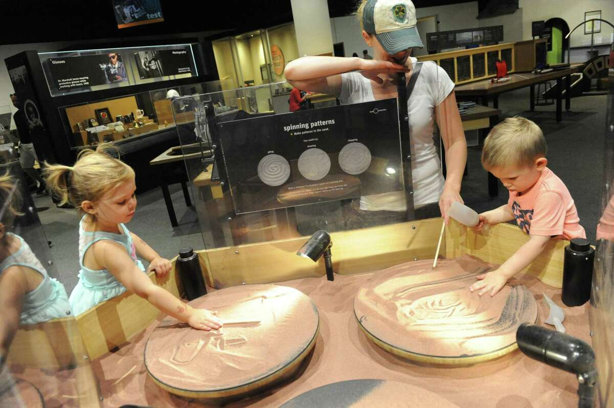 Jenny Paul of Colonie and her children Adalyn Paul, 3-years-old left, and Logan Paul, 2, play on the spinning patterns exhibit at MiScion Saturday July 2, 2016 in Schenectady, N.Y. (Michael P. Farrell/Times Union) ORG XMIT: MER2017121415363070