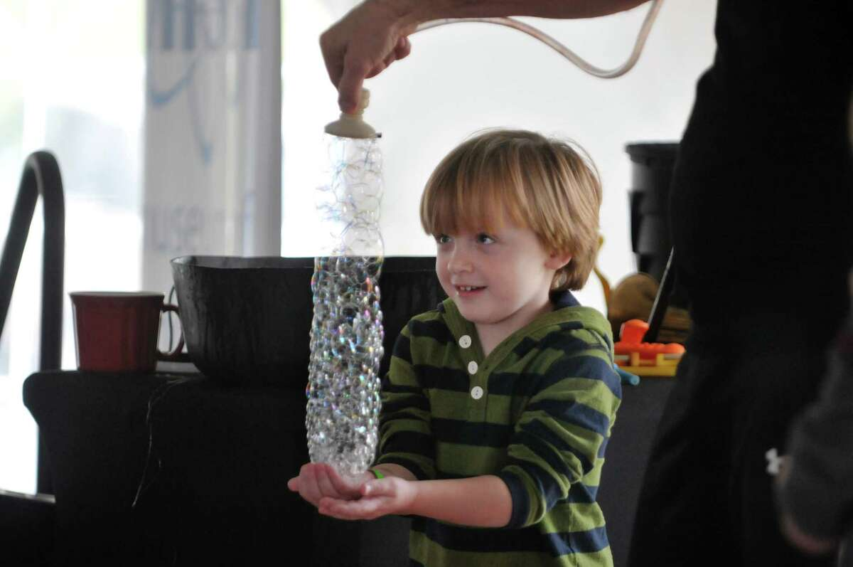 Miles Solotruck, 4, of Scotia holds a tower of bubbles as Jeff Boyer, of Jeff Boyer Productions puts on a show at the miSci Science Festival on Sunday, Nov. 9, 2014, in Schenectady, N.Y. This was the first year that miSci held the festival, which was made possible through a national grant. The festival took place Friday through Sunday, with 45 different area groups, organizations and businesses taking part to provide hands-on experiments for children. (Paul Buckowski / Times Union) ORG XMIT: MER2017121415370874